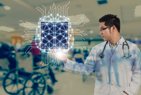 Foto de Asian Doctor with the stethoscope equipment hand holding the Artificial intelligence of brain technology over Abstract photo blurred of hospital background, AI and physician concept - Imagen libre de derechos