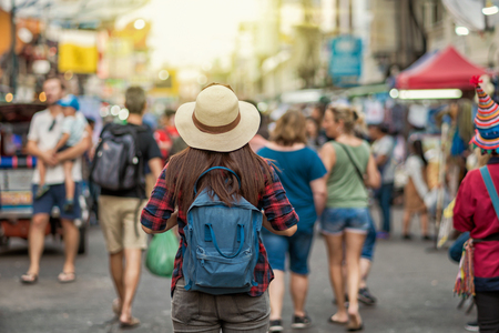 Photo pour Back side of Young Asian traveling women walking and looking in Khaosan Road walking street in evening at Bangkok, Thailand, traveler and tourist concept - image libre de droit