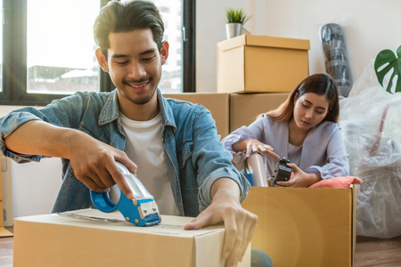 Foto de Asian young couple packing big cardboard box for moving in new house, Moving and House Hunting concept - Imagen libre de derechos