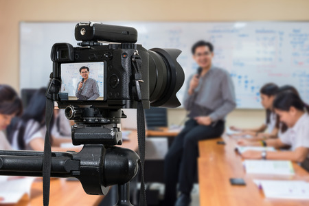 Foto de Professional digital Mirrorless camera on the tripod recording video blog of Asian teacher in the classroom - Imagen libre de derechos