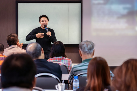 Foto de Asian Speaker or lecture with casual suit on the stage in front of the room presenting with the screen in the conference hall or seminar meeting room, business and education concept - Imagen libre de derechos