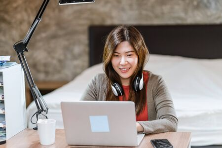 Photo for Asian business woman using technology laptop and working from home in indoor bedroom,freelance and entrepreneur,startups and business owner,lifestyle occupation,social distance and self responsibility - Royalty Free Image
