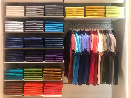 Foto de Multi color polo shirts on hanger and shelves for sale in store - Imagen libre de derechos