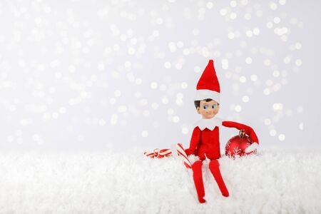 Photo for Christmas Elf sitting on a Snowy Shelf with Peppermint Sticks and Ornament - Royalty Free Image