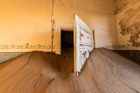 Photo for A photograph inside an abandoned house with an open white door submerged in the rippled desert sand, taken in the ghost town of Kolmanskop, Namibia. - Royalty Free Image
