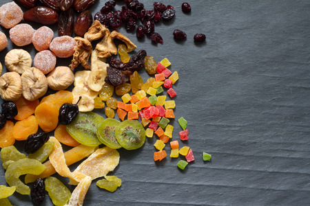Foto de Candied dried mixed assortment of exotic fruits on black marble - Imagen libre de derechos