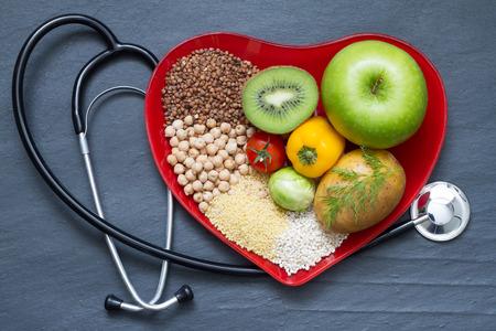Foto de Healthy food on red heart plate cholesterol diet concept - Imagen libre de derechos