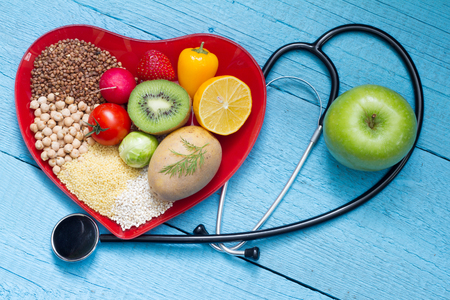 Foto de Food on heart plate with stethoscope cardiology concept - Imagen libre de derechos