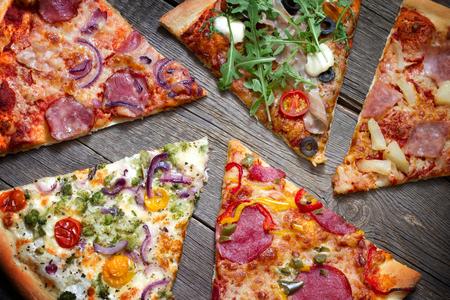 Photo pour Pieces of pizza of different types on old retro boards still life concept - image libre de droit