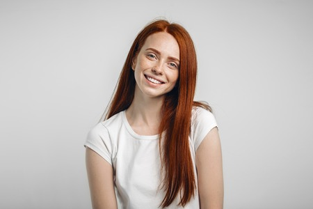 Foto de Headshot Portrait of happy ginger girl with freckles smiling looking at camera - Imagen libre de derechos