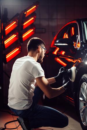 Photo pour Car detailing - man with orbital polisher in auto repair shop. Selective focus. - image libre de droit