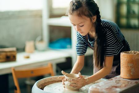 Photo pour Child sculpts from clay pot. modeling on potter wheel. - image libre de droit