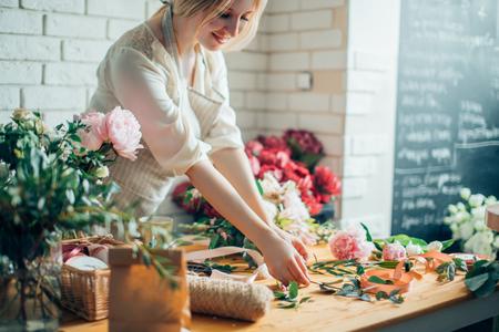 Foto de Florist workplace: woman arranging a bouquet with flowers - Imagen libre de derechos
