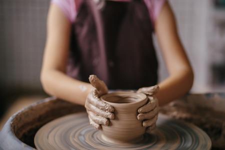 Foto de Hands of young potter, close up hands made cup on pottery wheel - Imagen libre de derechos