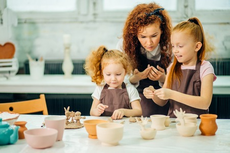 Photo pour redhead mother and two daughter mold with clay, pottery children - image libre de droit