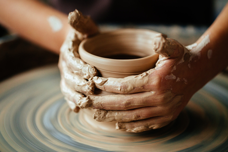 Photo pour Female potter working at throwing wheel at studio. Clay workshop - image libre de droit