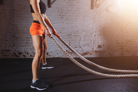 Foto de Young woman preparing to working out with battle ropes in cross fit gym - Imagen libre de derechos