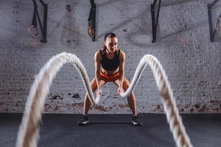 Foto de Young woman working out with battle ropes in cross fit gym - Imagen libre de derechos