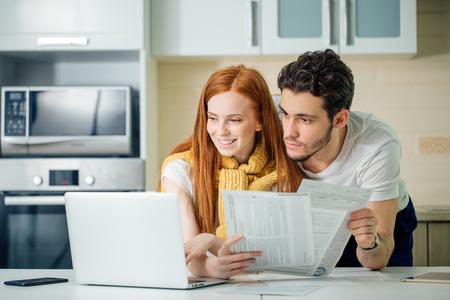 Photo pour Happy couple at home paying bills with laptop - image libre de droit