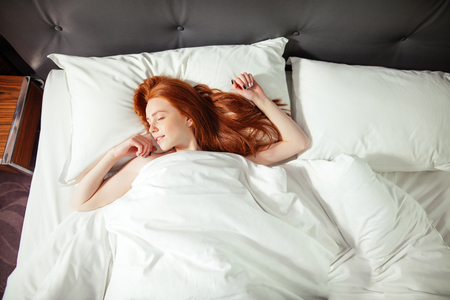 Photo pour sleeping young woman lies in bed with eyes closed. top view - image libre de droit
