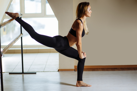Photo pour Girl smiling and looking in mirror while stretching body in fitness class - image libre de droit