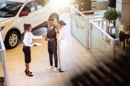 Photo for car salesman standing at dealership telling about features of car to customers - Royalty Free Image