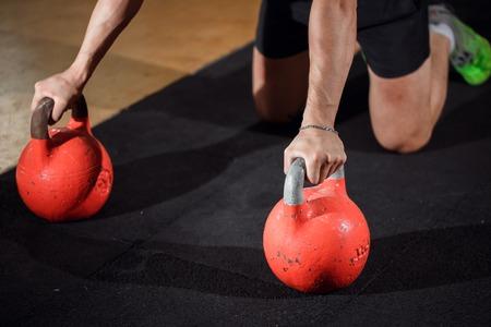 Foto de Gym man push-up strength pushup exercise with Kettlebell in a workout - Imagen libre de derechos