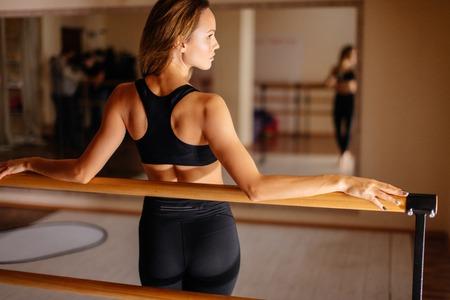 Foto de woman dancer posing near barre in ballet studio. - Imagen libre de derechos