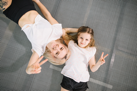 Foto de mother and little daughter playing at playground and lying on trampoline - Imagen libre de derechos