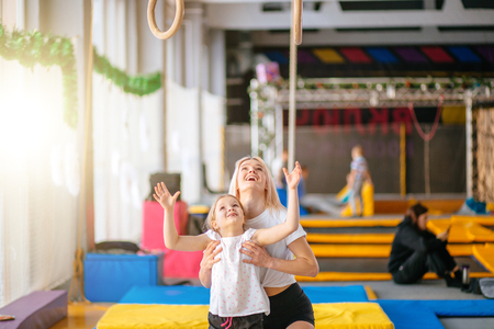 Mother helping daughter to play sports on gymnastic rings