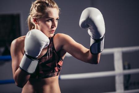 Foto de Female Boxer wearing gloves posing in boxing studio - Imagen libre de derechos