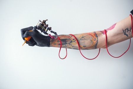 Photo pour hand tattoo artist with the tattoo machine - image libre de droit