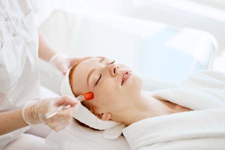 Photo pour Doctor applies Hydro gel Mask on the woman before making laser treatment. - image libre de droit