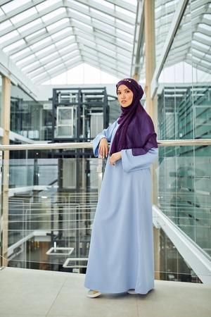 Foto de Portrait of a beautiful Arabian Woman in her 20th wearing Hijab and blue long dress posing for fashion magazine in modern interior. - Imagen libre de derechos