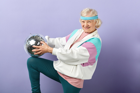 Foto de Positive glad elderly lady holds sparkling disco ball, dressed in trendy windbreaker of mint and pink colors, smiling at camera, being in high spirit - Imagen libre de derechos