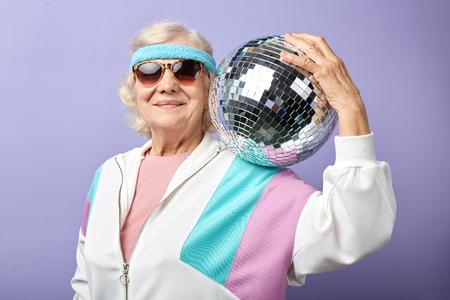 Photo pour Joyful smiling aged woman portrait dressed in sportswear, holding ball, set in purple studio. Age of health, leisure, entertainment in retirement - image libre de droit