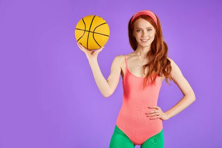 Foto für cropped shot of healthy athletic ginger girl holding ball in hand, standing ready to start volleyball game, shows strong muscules and biceps, has nice body shape, wears comfortable pink bodysuit, green leggins and white sport shoes. Studio shot, half-body view. - Lizenzfreies Bild