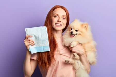 Photo pour red-haired pretty positive girl controlling pissing process of her pet. close up portrait isolated blue background - image libre de droit