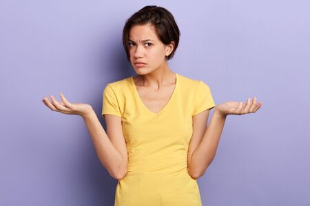 Foto de serious girl cannot understand her friend, woman being puzzled with suggestion, offer, close up portrait, isolated violet background, studio shot - Imagen libre de derechos