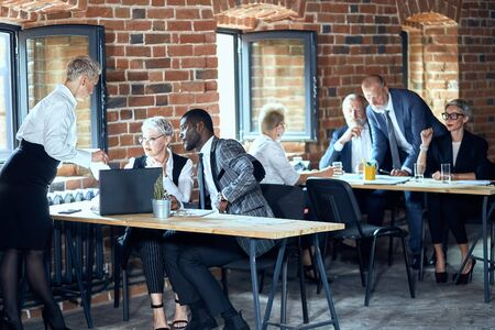 Photo for In the foreground two caucasian blond women and one african man work at table on laptop. On the background two caucasian blond men and two caucasian blond women work at table. - Royalty Free Image