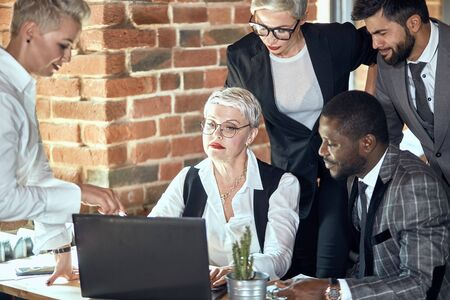 Photo for Three adult blonde women and dark haired men at table in office discuss project. Camera focused on blonde with glasses at laptop. Woman near points to monitor - Royalty Free Image