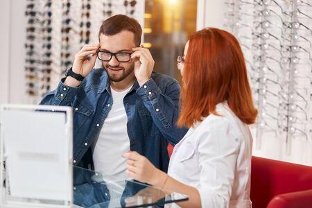 Foto de handsome male client enjoying choosing glasses at clinic, . bargain, medicine concept, close up photo - Imagen libre de derechos