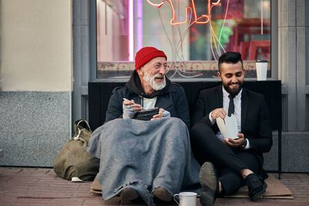 Photo for Smiling rich and poor men together sitting on street and eat while speaking. Happy despite social inequality - Royalty Free Image