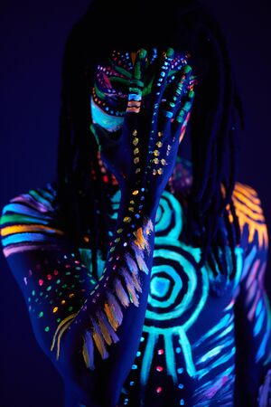 Photo for handsome african guy with UV body art close his face, colorful fantastic prints glows in darkness - Royalty Free Image
