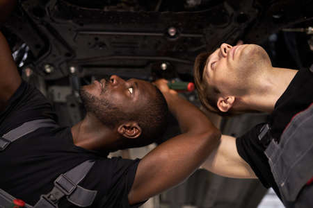 Photo pour two interracial car mechanics in uniform checking car in automobile service with lifted vehicle, african and caucasian men repair a car together - image libre de droit
