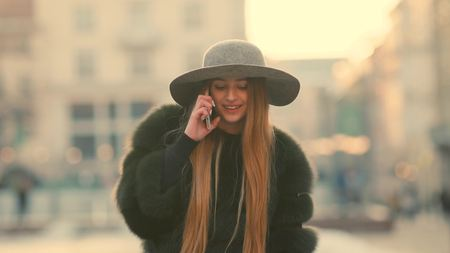 Foto de Young woman in a bright sunlight uses her phone smile talks in the phone - Imagen libre de derechos