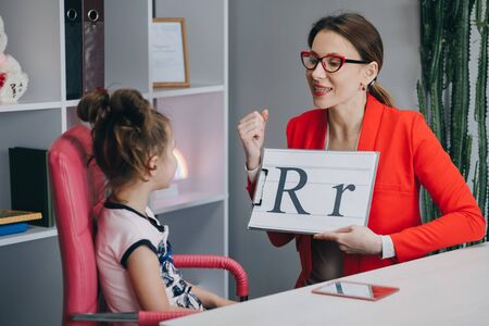 Foto de Speech therapist teaches the girls to say the letter R. Speech therapist holding letter R and girl back view - Imagen libre de derechos