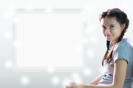 girl sitting against a white sheet. place for your inscription