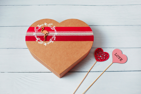 Photo for Heart shape gift box on wood background. Empty blank, vacant, hollow. Craft heart love gift box container and two heart. Holiday, happy Valentines day, christmas, thanksgiving day, birthday top view - Royalty Free Image