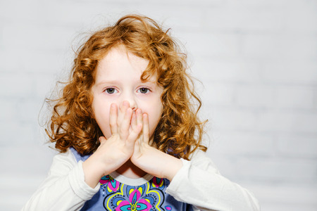 Photo for Little girl covering her mouth with her hands. Surprised or scared. On the light background indoors. - Royalty Free Image